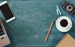 Image de vue supérieure de téléphone portable, de tasse de café et d'ordinateur portable au-dessus de fond de tableau noir Photos stock