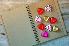 Image de vue supérieure des chocolats colorés de forme de coeur sur le carnet vide ouvert sur la table en bois Concept de célébra Photographie stock libre de droits
