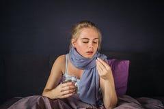 Image de younf et de regards en difficulté de femme à la capsule bleue Elle veut le manger Il y a verre de l'eau dans une autre m image stock