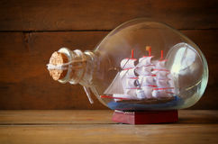 Image of decorative boat in the bottle on wooden table Royalty Free Stock Photos