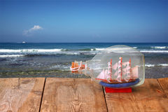 Image of decorative boat in the bottle on wooden table in front of sea. nautical concept. retro filtered image Royalty Free Stock Images