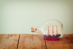 Image of decorative boat in the bottle on wooden table. nautical concept. retro filtered image Stock Photos