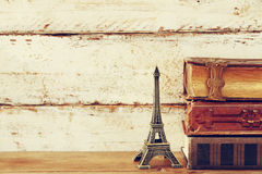 Image of decorative eiffel tower and vintage books. On wooden table. vintage filtered royalty free stock photo