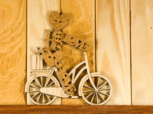 Image of decorative little man on a bicycle on wooden boards background. Stock Photos