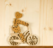 Image of decorative little man on a bicycle on wooden boards background. Royalty Free Stock Image