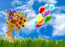 Image of decorative little man, flowers and baloons on a bicycle against the sky. Royalty Free Stock Photography