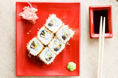 Image of delicious sushi wasabi and ginger on red plate with soy sauce and wooden chopsticks on white napkin background Royalty Free Stock Images