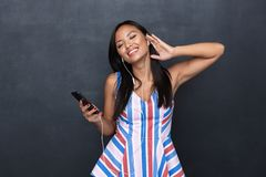 Image of delighted asian woman 30s wearing earphones listening to music on black smartphone standing isolated royalty free stock image