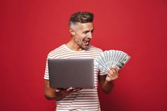 Image of delighted man in striped t-shirt smiling while holding. Fan of money banknotes and laptop isolated over red background stock photo