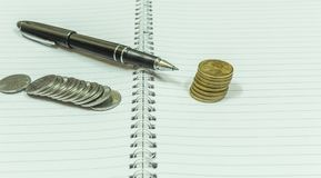 Image depicting blank spiral notebook with a black vintage pen. Placed over with india currency coins used for financial investments or calculation. With Royalty Free Stock Image