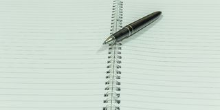 Image depicting blank spiral notebook with a black vintage penImage depicting blank spiral notebook with a black vintage pen place. Image depicting blank spiral Royalty Free Stock Photos