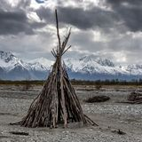 Alaskan TeePee built in a dry riverbed with majestic mountains as a backdrop. The image depicts a beautiful Alaskan scene in a dry riverbed. These Teepees are royalty free stock photos