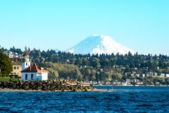 Alki Lighthouse in the shadow of Mount Rainier on Puget Sound stock image