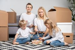 Image des ajouter heureux aux enfants mangeant du riz avec des crevettes se reposant sur le plancher photographie stock