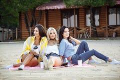 Image des amis heureux se trouvant sur l'herbe et le sourire Images stock