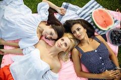 Image des amis heureux se trouvant sur l'herbe et le sourire Image libre de droits