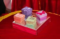 Image des anneaux de mariage dans un boîte-cadeau sur le plateau en plastique de fleur, le foyer choisi et le fond brouillé Photographie stock