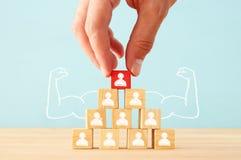 Image des blocs en bois avec des icônes de personnes au-dessus de table, établissant une équipe forte, des ressources humaines et Photo stock