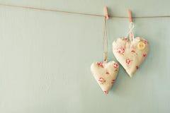 Image des coeurs de tissu accrochant sur la corde devant le fond en bois bleu Rétro filtré Photos stock