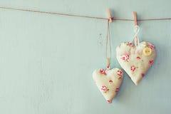 Image des coeurs de tissu accrochant sur la corde devant le fond en bois bleu Rétro filtré Photo stock