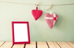 Image des coeurs rouges de tissu accrochant sur la corde et le cadre vide devant le fond en bois Rétro filtré Photo libre de droits