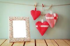 Image des coeurs rouges de tissu accrochant sur la corde et le cadre vide devant le fond en bois Rétro filtré Image stock