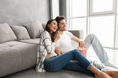 Image des couples de sourire se reposant sur le plancher près du sofa à la maison et du l Photos stock