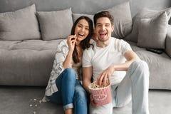 Image des couples gais de sourire se reposant sur le plancher près du sofa à h Photo libre de droits