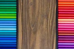 Image des crayons multicolores, deux rangées verticales, fond en bois Images stock