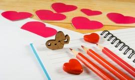 image des enveloppes, des carnets, des crayons, et des coeurs de papier sur un plan rapproché en bois de table Photo libre de droits