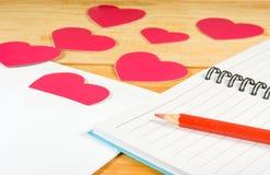 image des enveloppes, des carnets, des crayons, et des coeurs de papier sur un plan rapproché en bois de table Photos libres de droits
