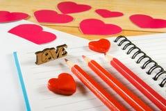image des enveloppes, des carnets, des crayons, et des coeurs de papier sur un plan rapproché en bois de table Photographie stock libre de droits