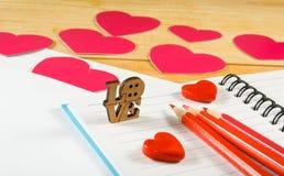image des enveloppes, des carnets, des crayons, et des coeurs de papier sur un plan rapproché en bois de table Images stock