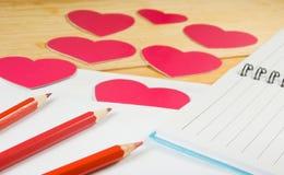 image des enveloppes, des carnets, des crayons, et des coeurs de papier sur un plan rapproché en bois de table Photo stock