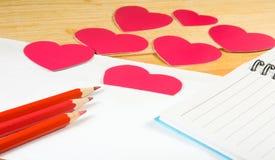 image des enveloppes, des carnets, des crayons, et des coeurs de papier sur un plan rapproché en bois de table Image libre de droits
