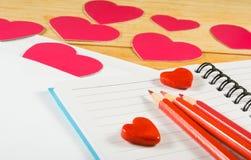 image des enveloppes, des carnets, des crayons, et des coeurs de papier sur un plan rapproché en bois de table Photographie stock
