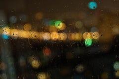 Image des gouttes de pluie sur la fenêtre la nuit dans la ville image libre de droits