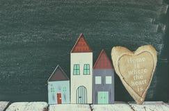 Image des maisons de vintage et du coeur colorés en bois de tissu sur la table en bois devant le tableau noir rétro image filtrée Photo stock