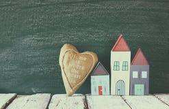 Image des maisons de vintage et du coeur colorés en bois de tissu sur la table en bois devant le tableau noir rétro image filtrée Photographie stock