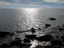 Image des pierres dans un lac du nord tranquille au coucher du soleil Images libres de droits