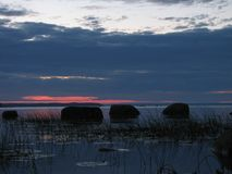 Image des pierres dans un lac du nord tranquille au coucher du soleil Images stock