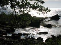 Image des pierres dans un lac du nord tranquille au coucher du soleil Photos libres de droits