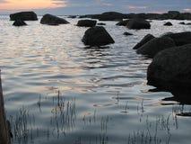 Image des pierres dans un lac du nord tranquille au coucher du soleil Image libre de droits