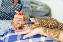 Image detail of henna being applied to hand. Royalty Free Stock Images