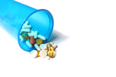 Image of different pills spilling out of a plastic glass Stock Images