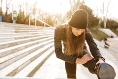 Image of disabled healthy girl in sportswear, training and stretching prosthetic leg on railing in stadium outside. Image of disabled healthy girl in sportswear stock photo