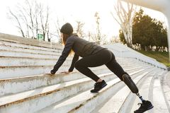 Image of disabled running girl with prosthetic leg in sportswear. Exercising at the stairs outdoors stock photography