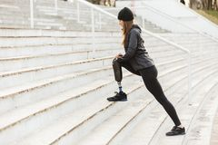Image of disabled running girl with prosthetic leg in sportswear. Working out at the stairs in stadium royalty free stock image