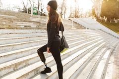 Image of disabled running girl with prosthetic leg in sportswear. Walking up the stairs in street royalty free stock photography