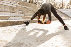 Image of disabled sportswoman in black tracksuit having prosthetic leg, exercising with slopes and stretching body outdoors. Image of disabled sportswoman in stock images